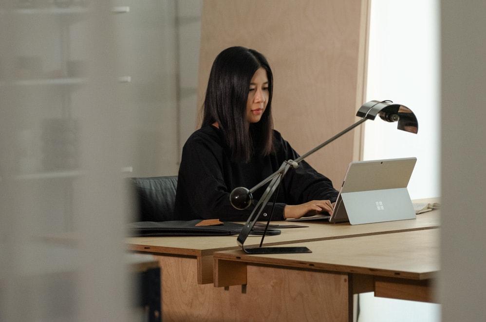 سيدة تعمل على جهاز Surface الخاص بها على مكتبها