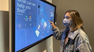 Aleenah Ansari interacts with the screen of a SmartBuilding services kiosk in the lobby of a Microsoft building.