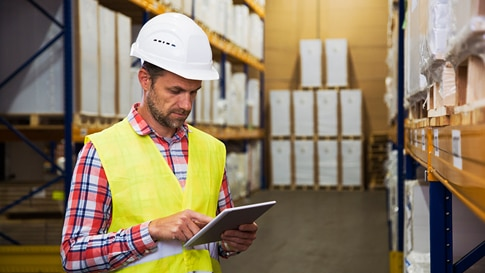A person in a warehouse wearing a hardhat and safety vest holding a tablet.