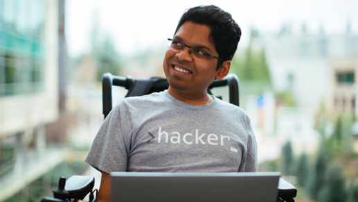 A person in a wheelchair holding a laptop on their lap.